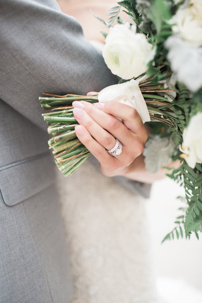 bride holding wedding flowers and engagement ring