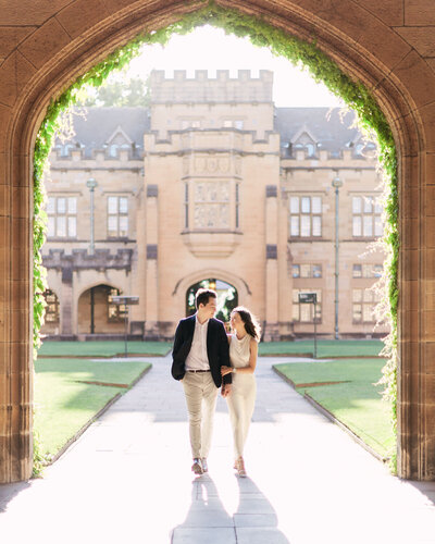 Couple walking beneath archway holding hands during their engagement shoot at Sydney University