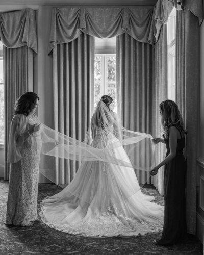 mother of the bride and maid of honor fluffing brides veil at the Ledges in Huntsville Alabama