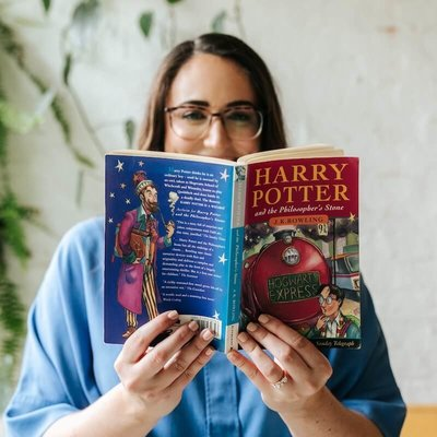 Charlotte Isaac holding a book, Harry Potter and the Philosophers Stone, partially covering her face