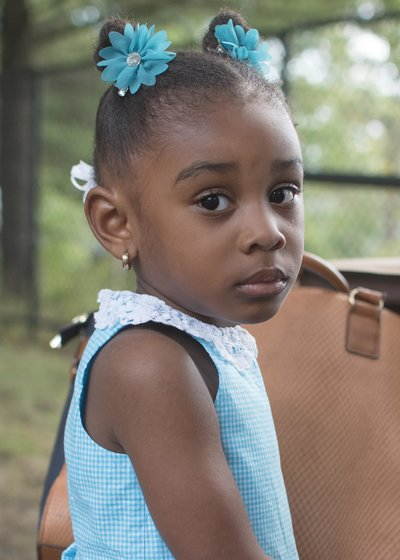 young african american toddler in a blue dress and blue hair clips  looking at the camera