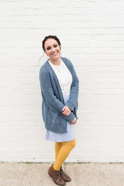 woman wearing mustard yellow tights and a blue polka dot dress is standing against a white brick wall and smiling at a camera in Nashville