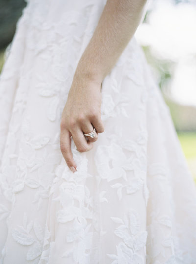 Detail wedding shot of bride holding dress with rose gold ring