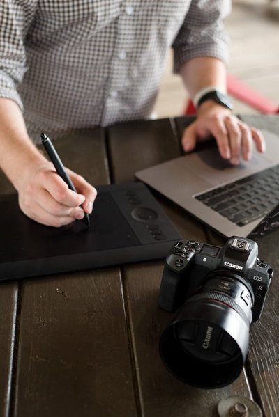photographer edits on wacom tablet laptop with camera
