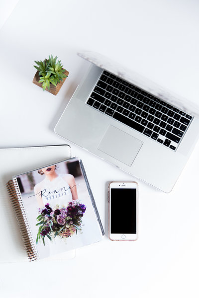 Flatlay of a laptop and Riane Roberts Photography course book