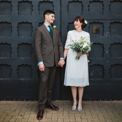 Photograph of vintage styled bride and groom laughing after relaxed Suffolk wedding ceremony