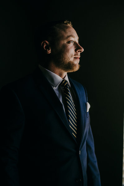 A groom wears a navy suit and striped tie