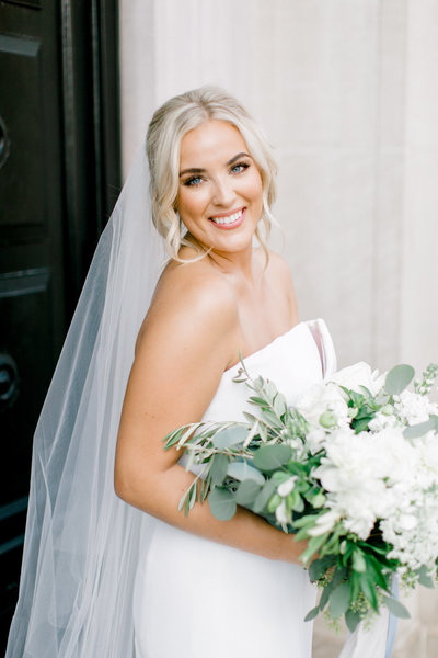 blond bride in updo holding flowers