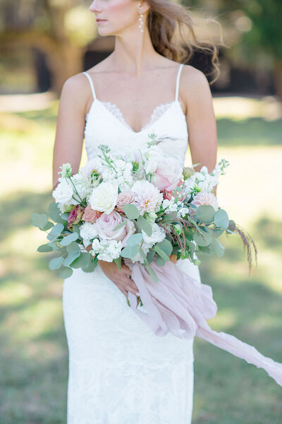 Fresh spring bridal bouquet with trailing silk ribbons in mixed pink hues