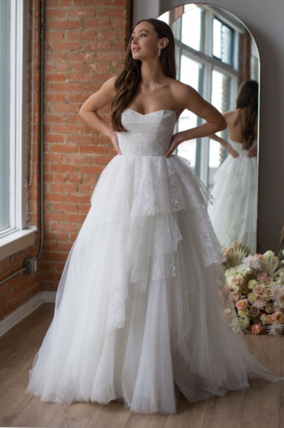 A unique balance between feminine and modern; this gown combines asymmetrical layering and mixed fabrics of beaded lace and tulle. The clean lines and delicate draping of Romy's bodice make this gown a bride's dream come true.
