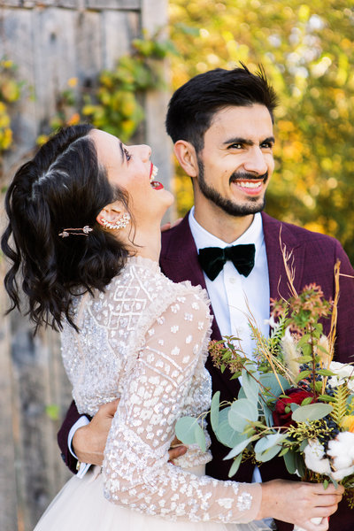 Young wedding couple laughing together with bride wearing diamon ear cuff and groom in a maroon suit.