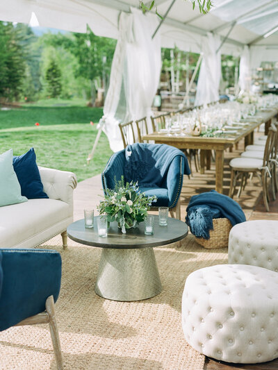 Reception seating area under white tent, blue chairs, white poofs, and coffee table