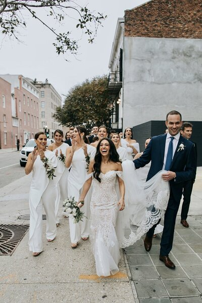 Groom carries brides dress as they walk to the ceremony, bridesmaids in white jumpsuits