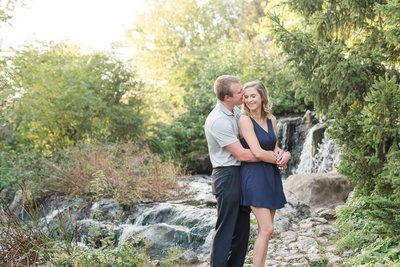 Engaged couple embracing near a waterfall during sunset.