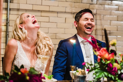 Bride and Groom laughing together at head table with floral bouquet in front