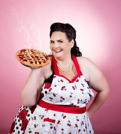 Woman in a apron with a vintage hairdo holding a pie posing for a pinup photo at boudoir and pinup by Janet Lynn Photography