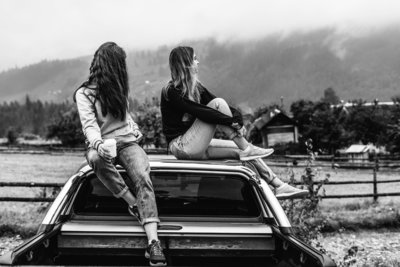 two-women-sitting-on-vehicle-roofs-2409681 2