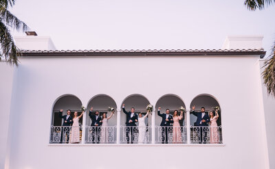 bridal party standing on balcony with arms raised above their heads