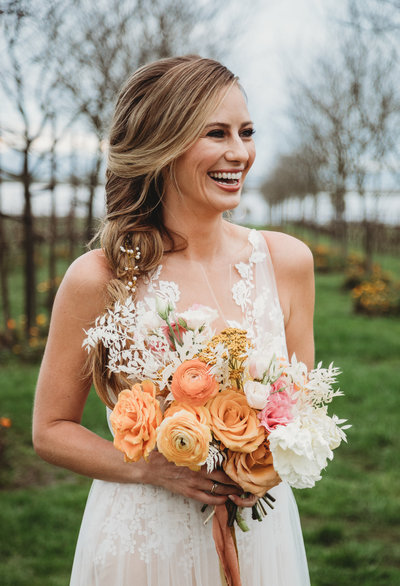 Bride smiling and holding spring bouquet at Jacuzzi Vineyard in Napa