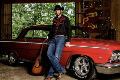 Country music portrait Chance Moore standing next to red classic car guitar leaning on car door beside him parked inside barn trees through entrance behind him