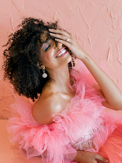 Woman laughing in bright pink dress