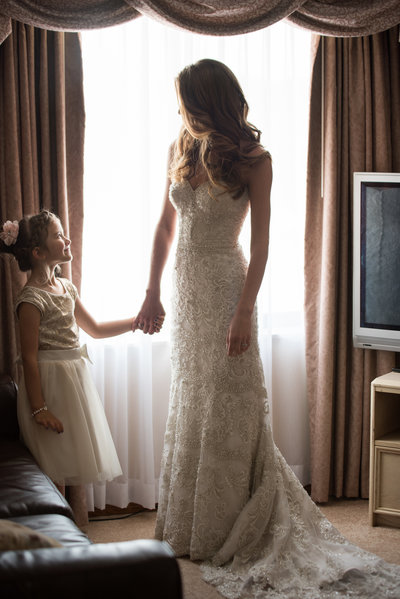 bride looking at little girl in fornt of window