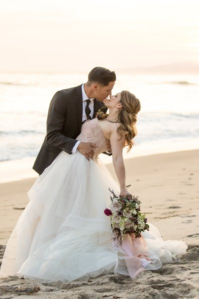 Handsome groom dipping Beautiful Bride on the beach in Santa Barbara, California
