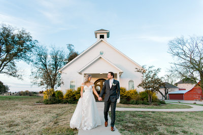 bride and groom walking in front of church at Rustic Grace Estate in Van Alstyne Texas