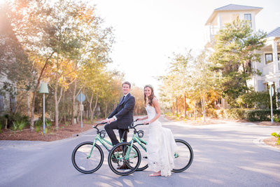 seaside florida wedding bride and groom on bicycles