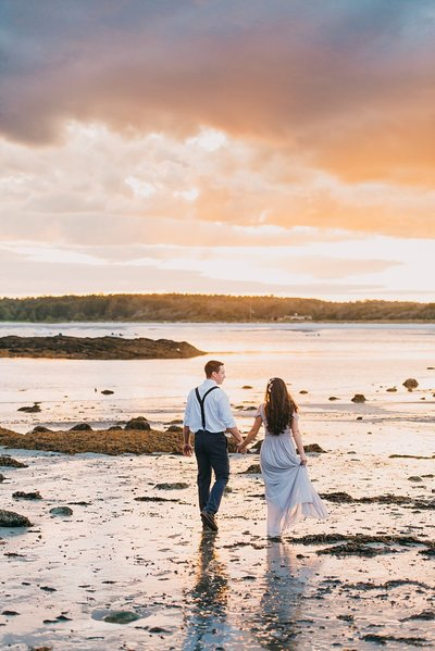 Couple walks along the beach at sunset in Maine