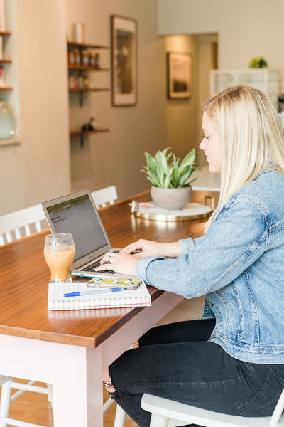 woman sitting at desk typing on laptop