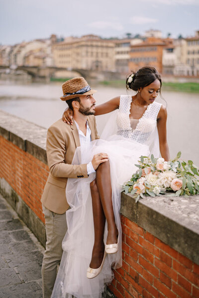 african-american-bride-sits-brick-wall-caucasian-groom-hugs-her-embankment-arno-river-overlooking-city-bridges-interracial-wedding-couple_278455-23