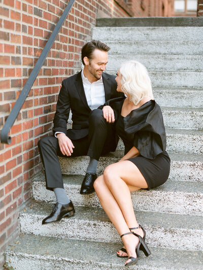 City Engagement Photograph on steps while wearing black tuxedo and black cocktail dress