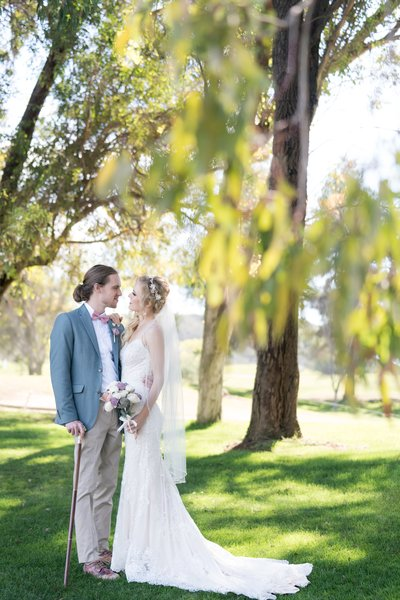 Couple standing under tree at their wedding at Temecula Creek Inn