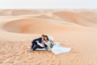 Wedding couple posing in front of sweetheart table overlooking Arabian desert dunes, photoshoot in Dubai organized by Lovely & Planned