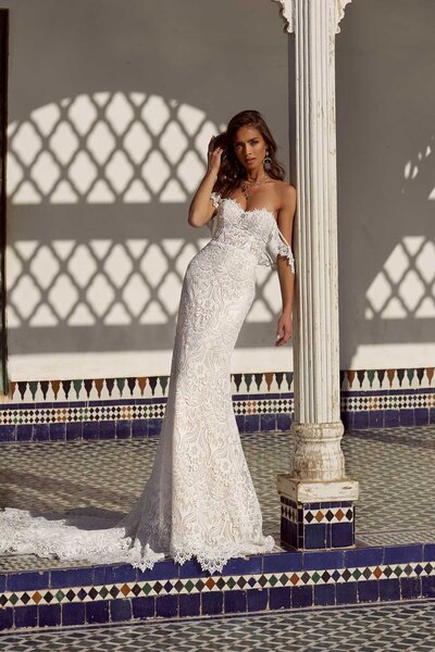 Charming like a goddess against the Marrakech sunlight is Andie. Her sensory baroque lace hugs perfectly to the female form, in all the right places, before streaming from the knee down and pooling into a long scalloped edged train. Andie's structured bodice nips in the waist allowing the sheer lace to continue through to a curved back. The Nude undertones warm and accentuate the intriguing embroidered lace as does the sand alternative. Draping stylishly from the bodice and off-the-shoulder are sheer lace straps giving brides-to-be a bohemian option or a classic strapless silhouette. Andie's unique lace creates intrigue and mesmerise – she is for the bride who cherishes every longing moment of an evening under the stars celebrating love.