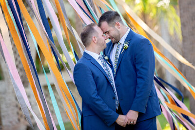 Two grooms embrace in front of a colorful ribbon display at Atalaya Castle
