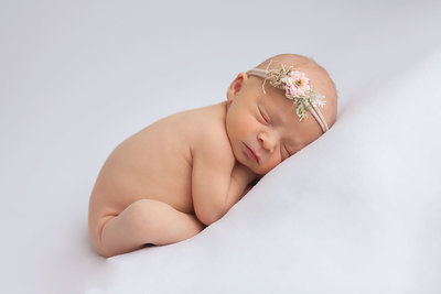 newborn baby girl on white background curled up on tummy-1
