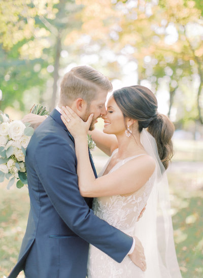 bride embraces grooms face as they smile at each other forehead to forehead
