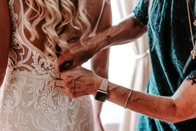 woman buttoning up bride's wedding dress