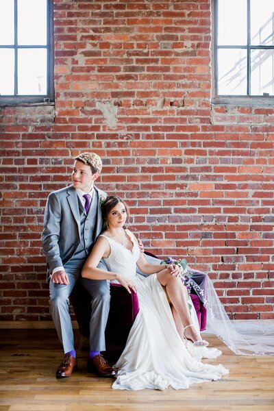 bride and groom sitting in front of brick wall by Knoxville Wedding Photographer, Amanda May Photos