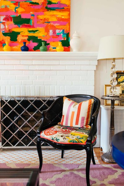 A white brick fireplace with colorful artwork and black chair.