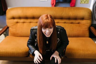 Image of Sarah Kenyon laughing on mustard couch wearing leather jacket