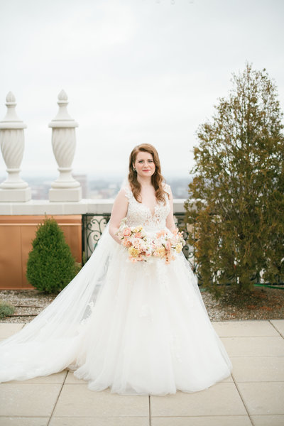 bride wearing a lace wedding dress stands on top of the balcony of the brown hotel holding bridal bouquet by roots floral design