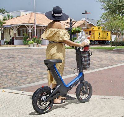 Lady strolling with Blue Go-Bike M3 wearing hat as she leaves the market with her groceries