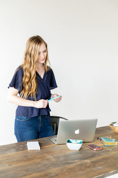 Blonde woman standing behind a Mac laptop and antique, wooden desk with a pen in her hand