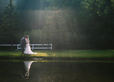 A groom embraces his bride by a pond. A shaft of light highlights the loving couple just married.