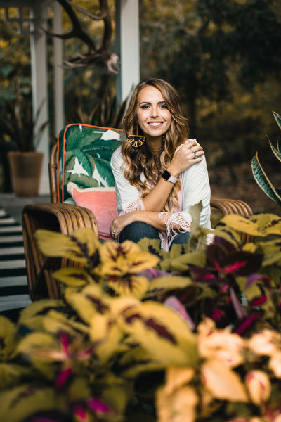 Image of Candice sitting in a tropical print chair smiling