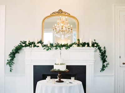 Gadsden House Wedding  Cake and Fire Place Mantle with Gold Mirror Greenery Garland Pillar Candles
