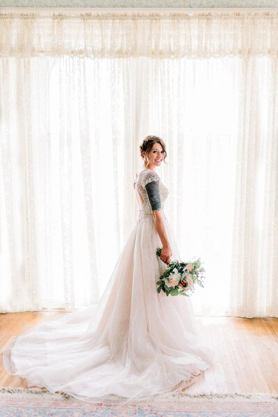 bride stands in front of window